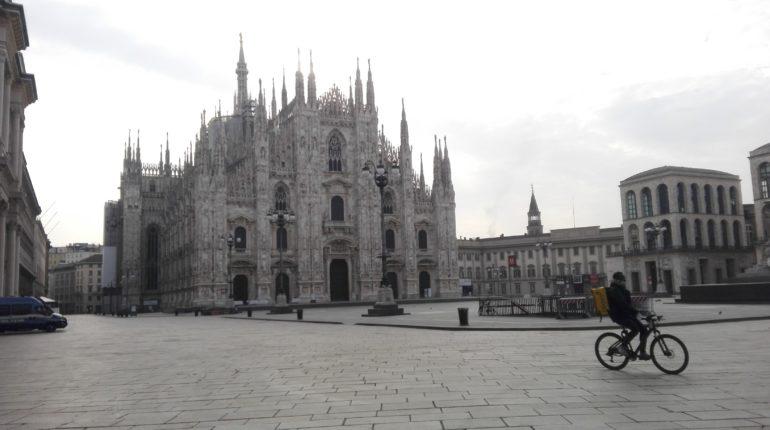 Un rider corre per piazza Duomo al tempo del coronavirus