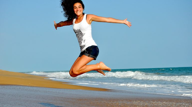 Una ragazza in salute salta sulla spiaggia e fa sport