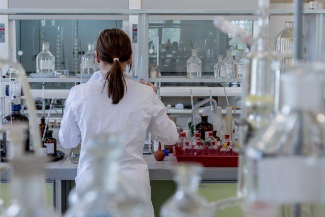 Una giovane ricercatrice, girata di spalle, lavora in laboratorio.