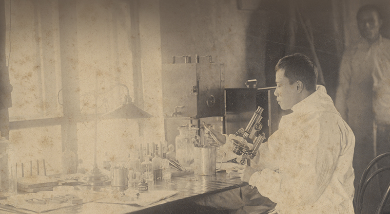 Il dottor Wu Lien-Teh mentre lavora al microscopio in Cina nel 1911